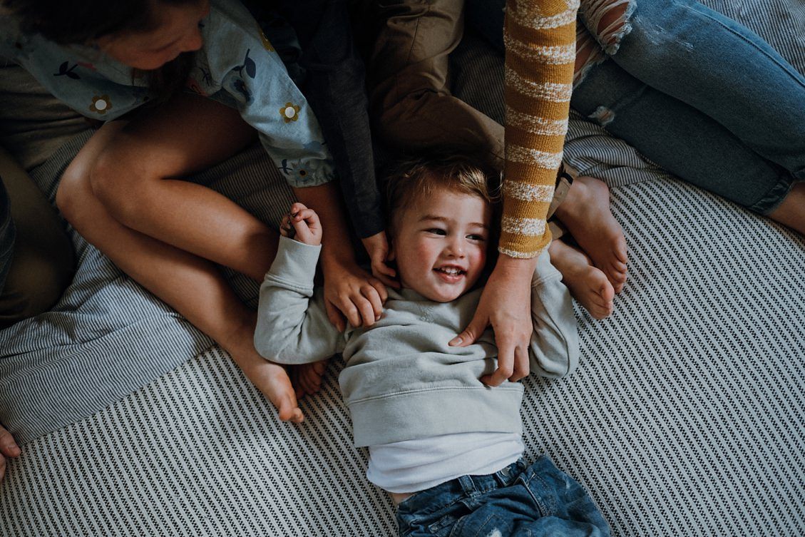 Boy-cuddled-by-family-on-bed