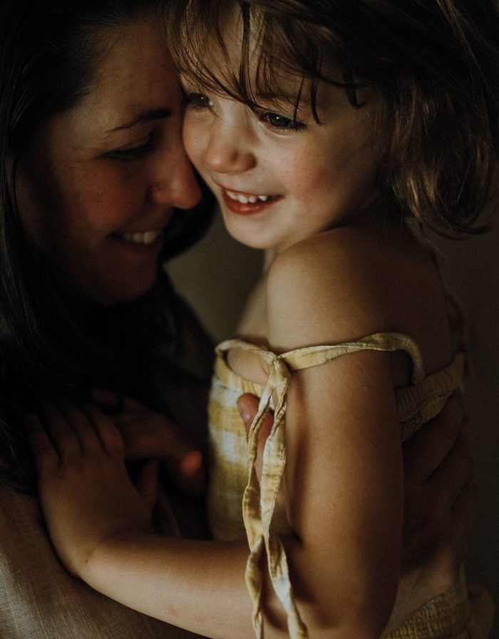 girl-and-mum-cuddling-smiling