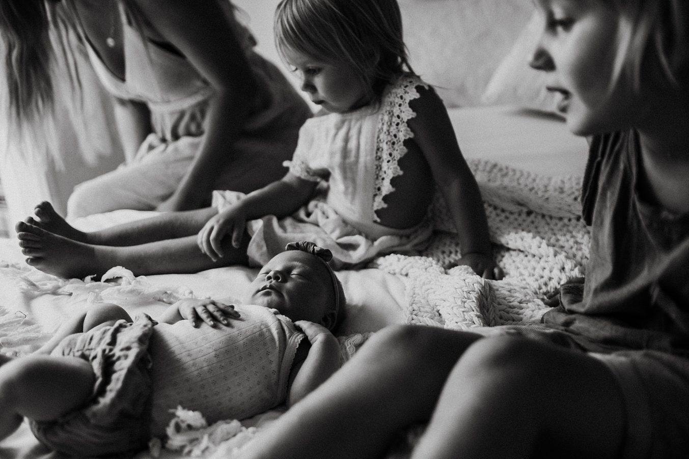 newborn-siblings-on-bed-black-white
