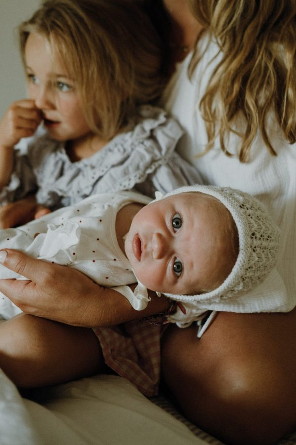 Baby with bonnet in mums arms